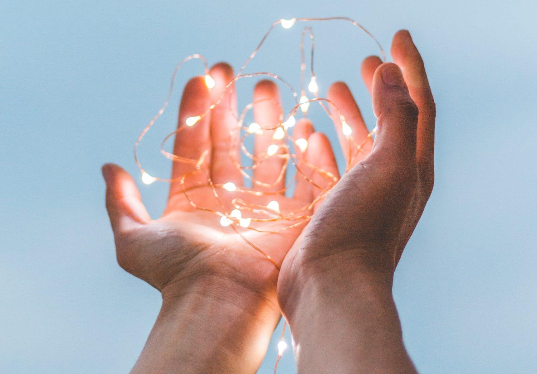 open hands holding fragile light